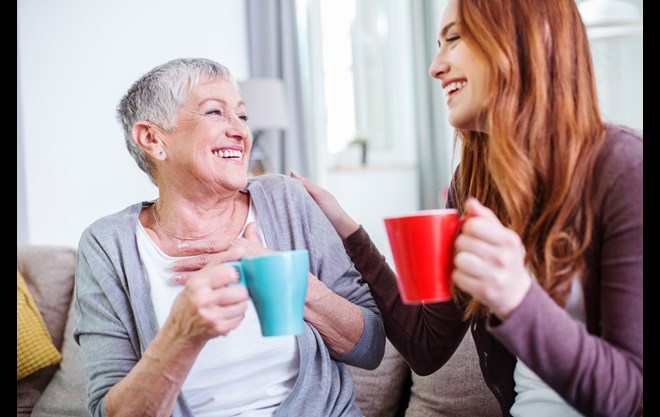 Older and younger woman laughing and drinking coffee