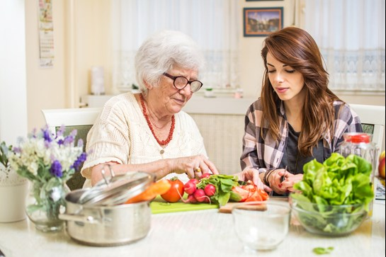 Elderly lady and young lady preparing vegetables in a kitchen
