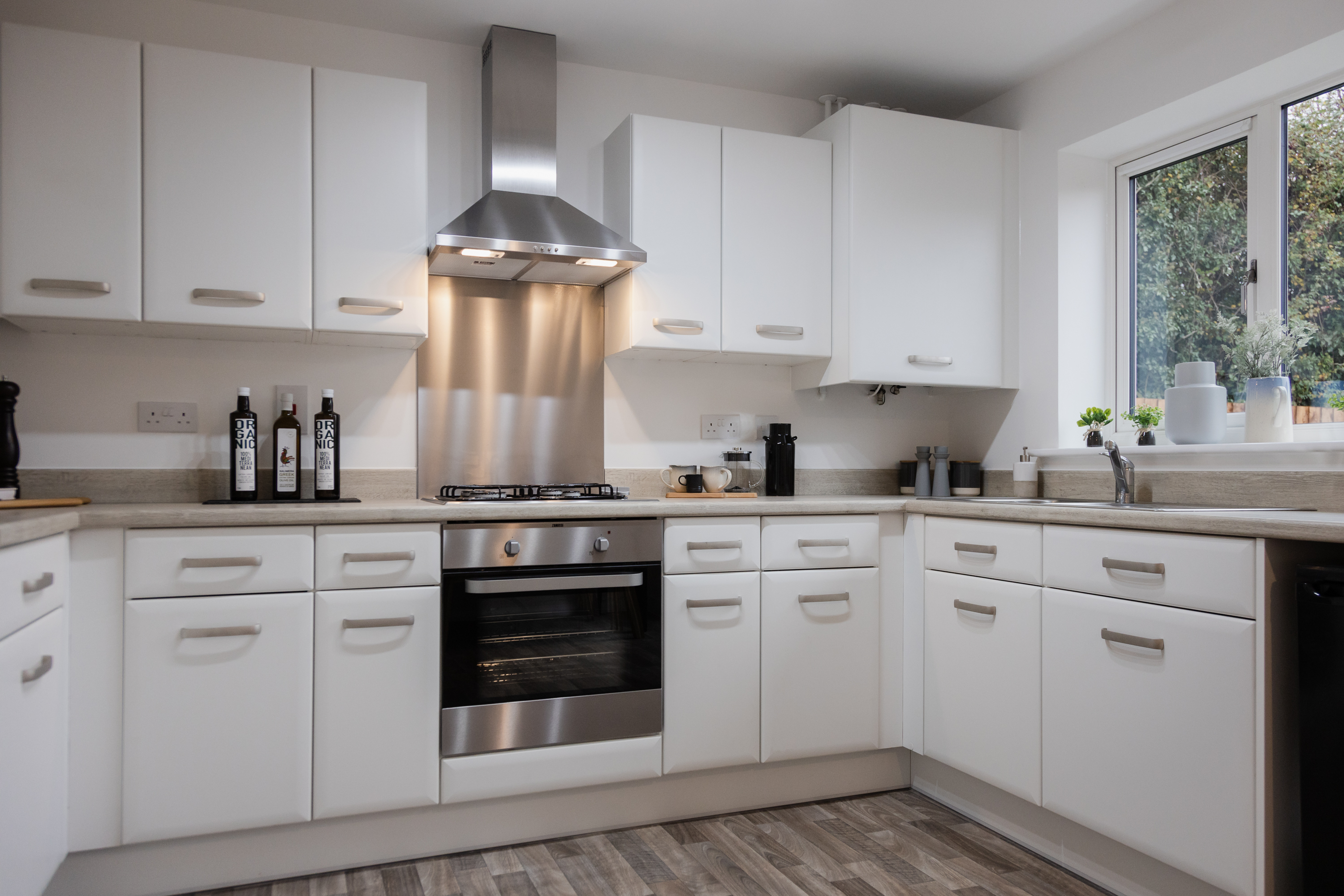 A modern kitchen with white door front, stone colour worktops and stainless steel accessories.