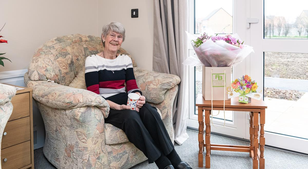 Willow Court resident sits in a chair in her room.
