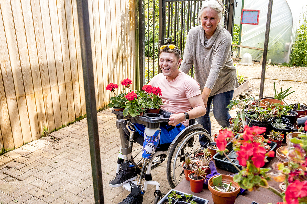 Young man in a wheelchair working in an allotment potting shed